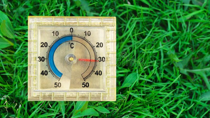 Square thermometer on the grass in the summer. So close stock images