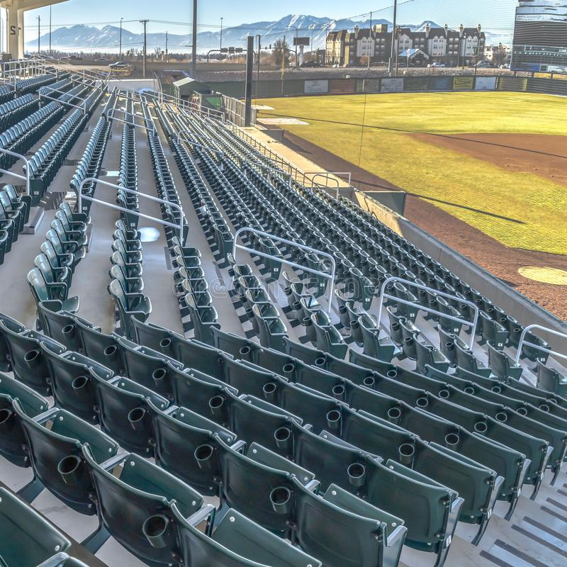 Square Tiered seating and viewing rooms on a baseball field viewed on a sunny day. Building and snow caped mountain against blue sky can be seen in the stock image