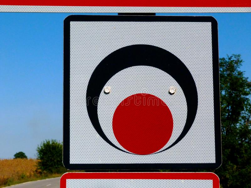 square traffic sign with black, red and white circles and blurry blue background stock photography