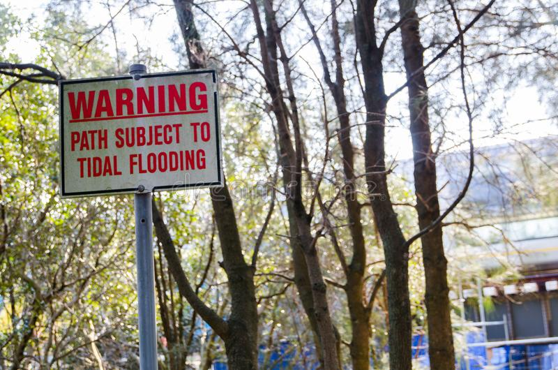 Square warning sign `Path Subject to tidal flooding` in a garden. stock photo