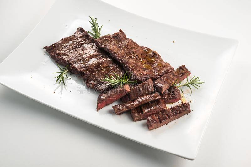 Meat dish Skirt Steak. Square white plate of sliced skirt steak and rosemary royalty free stock photo