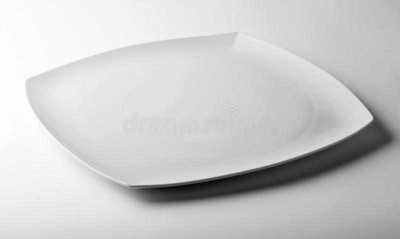Square white plate on white table royalty free stock photo