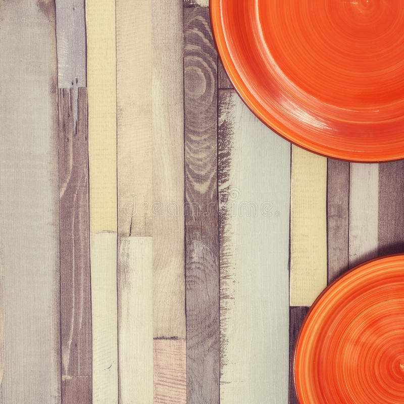 Square wooden background with two bright red plates. Toned image stock photo