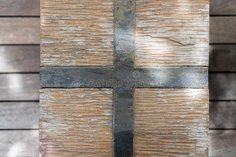 Square of wooden texture with a dark and rusty metal cross in the center. A square of wooden texture with a dark and rusty metal cross in the center stock photo