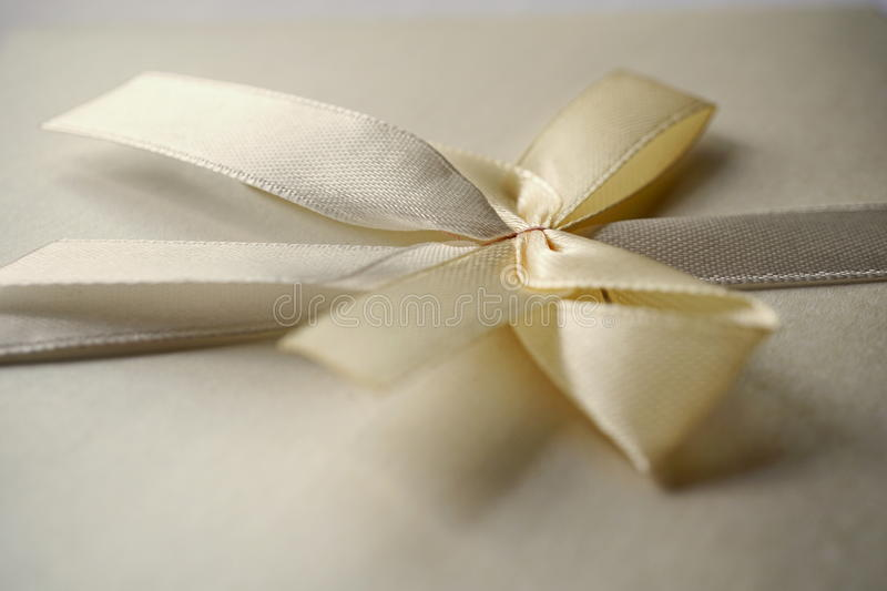 Squared silver envelope with pearly ribbon and topknot as an example of typical wedding invitation and wedding announcement cover. Squared silver envelope with stock photo