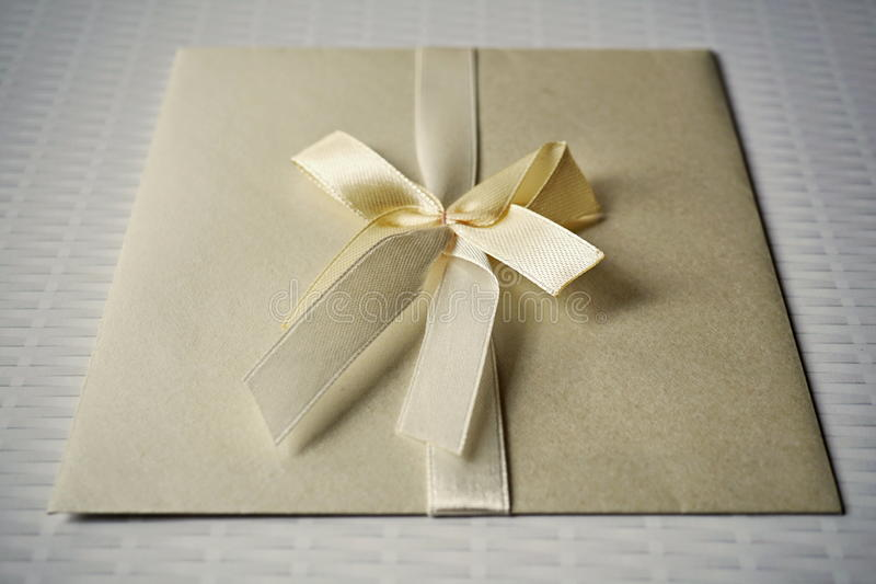 Squared silver envelope with pearly ribbon and topknot as an example of typical wedding invitation and wedding announcement cover. Squared silver envelope with stock images