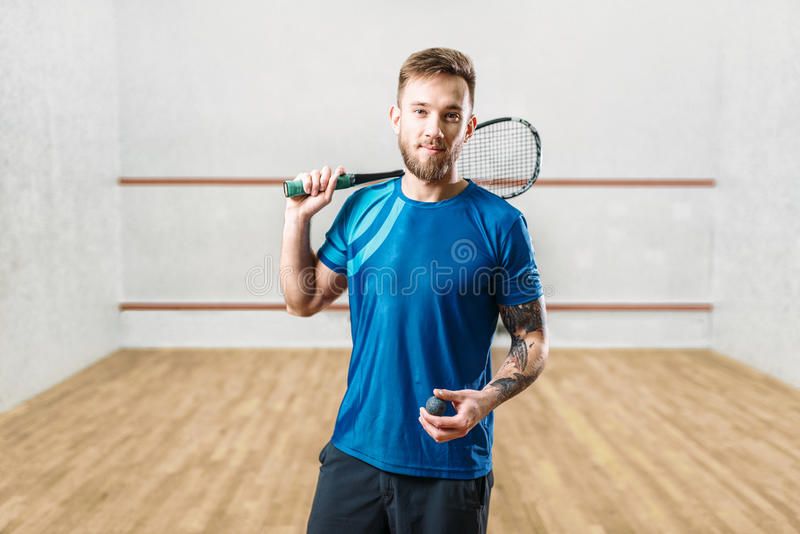 Squash game player with racket and ball in hands stock images