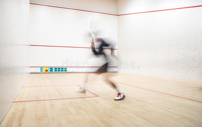 Squash player in action on a squash court royalty free stock photography