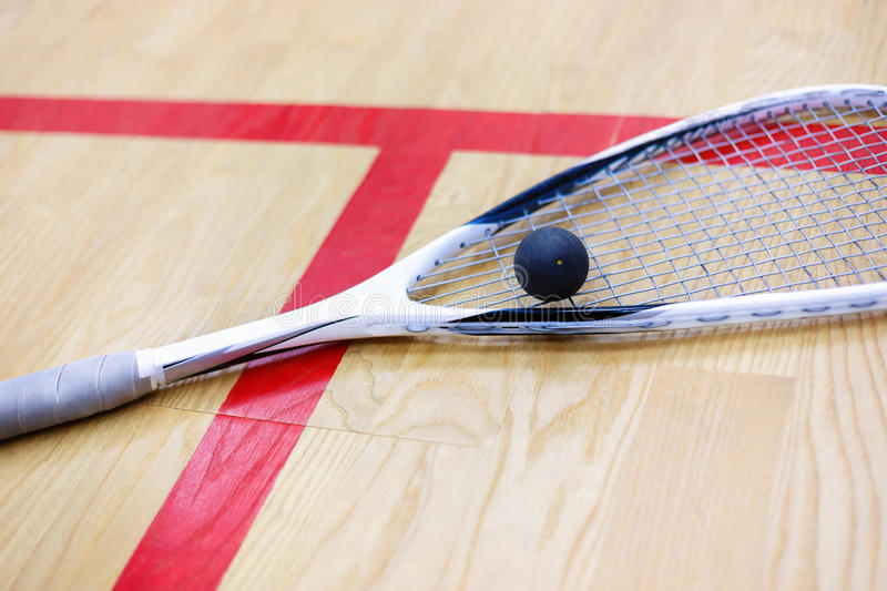 Squash racket and ball on the court stock photography