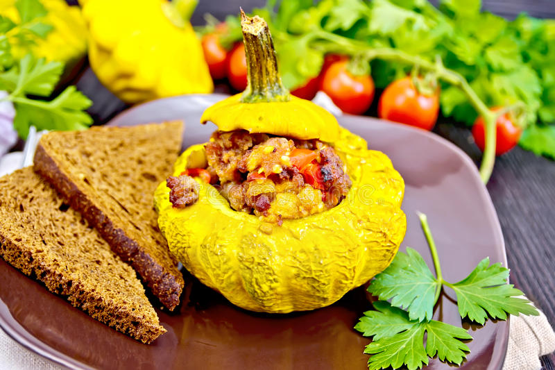 Squash yellow stuffed with meat and vegetables on dark board royalty free stock photos