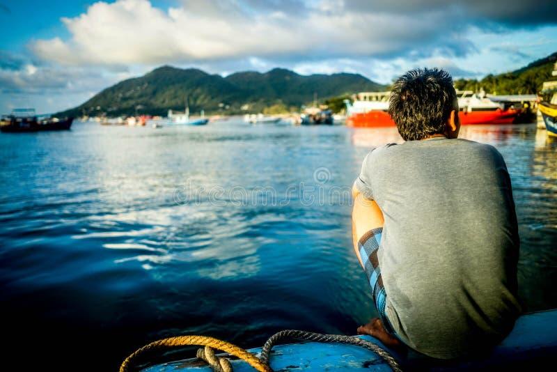 Squatting masculino adulto em um cais ao lado dos navios entrados e da água calma bonita imagem de stock royalty free
