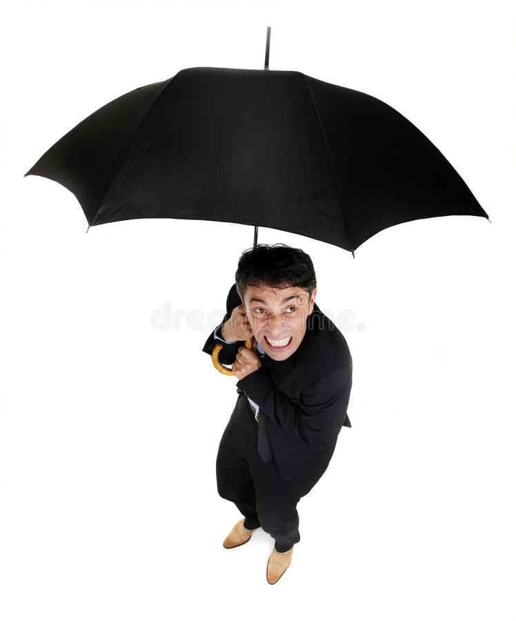 Squeamish business cowering under. Humorous high angle full length portrait of a squeamish business cowering under an umbrella as he looks up at the inclement stock photo