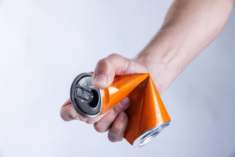 Squeeze aluminium can. Rumple, crumple aluminium can with one hand stock images