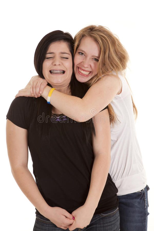 Squeeze tight neck. A teen girl giving her friend a tight hug around her neck royalty free stock photography