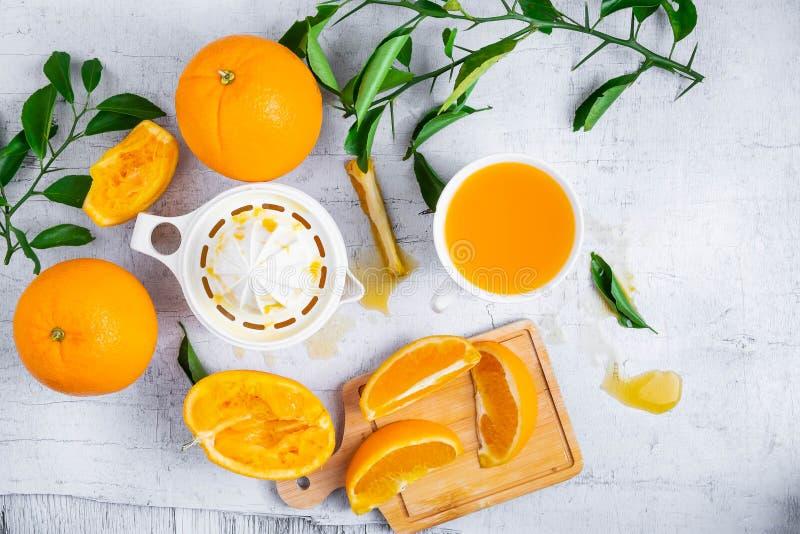 Squeezed orange juice and fresh oranges fruits on white wooden t royalty free stock image