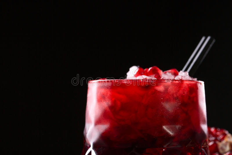 Squeezed pomegranate juice with crushed ice and black straws on a black background. Organic and benefit garnet beverage. royalty free stock photography
