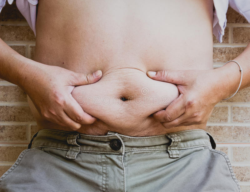 Squeezing belly fat around belly button.  royalty free stock image