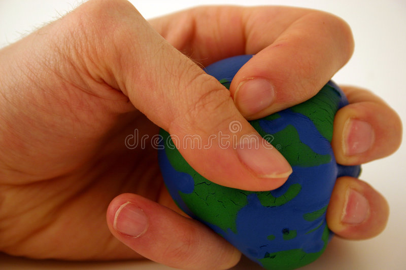 Squeezing the earth metaphor royalty free stock images