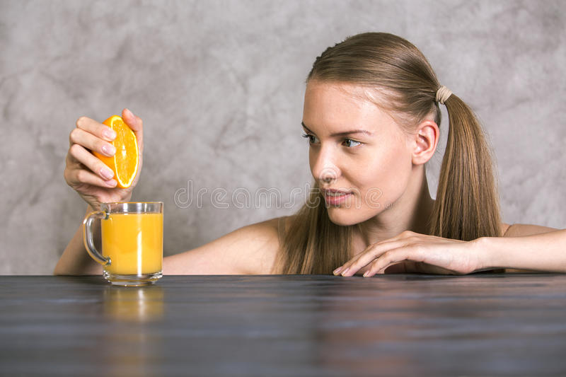 Squeezing orange on table royalty free stock photos