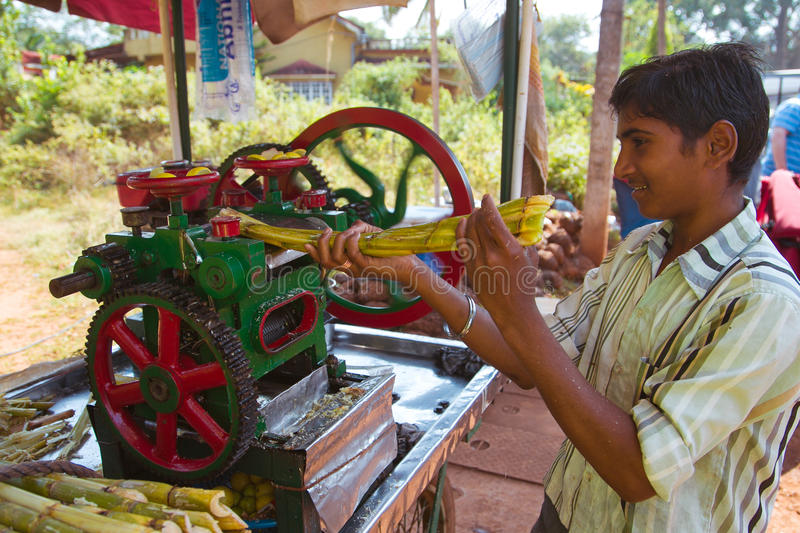 Squeezing sugar cane juice. Boy squeezes cane juice. India-Goa stock photos