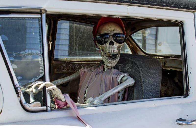Squelette dans des lunettes de soleil conduisant une voiture photo libre de droits