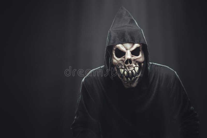 Squelette dans une robe longue noire se tenant sous des rayons photographie stock