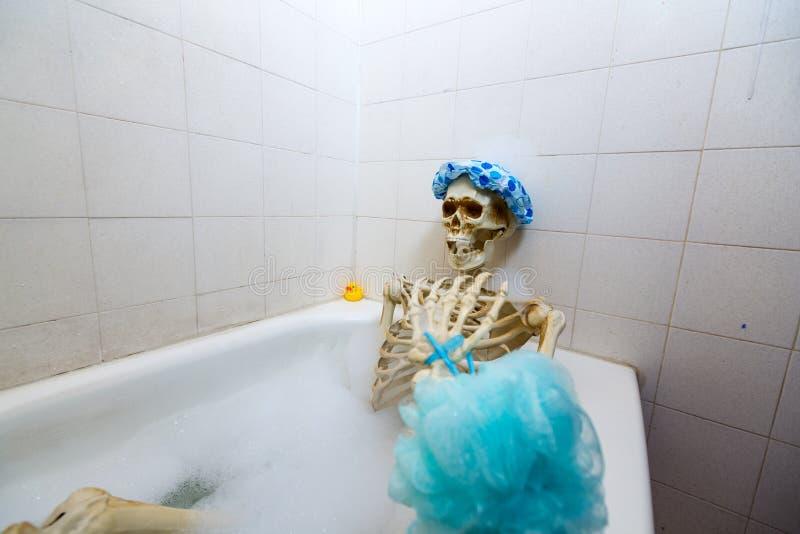Squelette osseux prenant un bain moussant dans un baquet sale blanc cassé sale photos libres de droits
