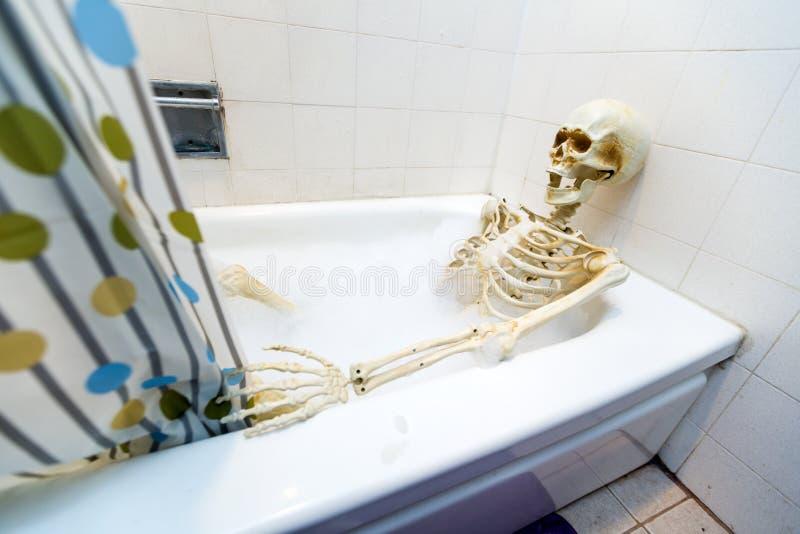Squelette osseux prenant un bain moussant dans un baquet sale blanc cassé sale photo libre de droits