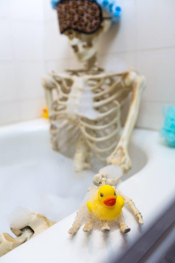 Squelette osseux prenant un bain moussant dans un baquet sale blanc cassé sale images libres de droits