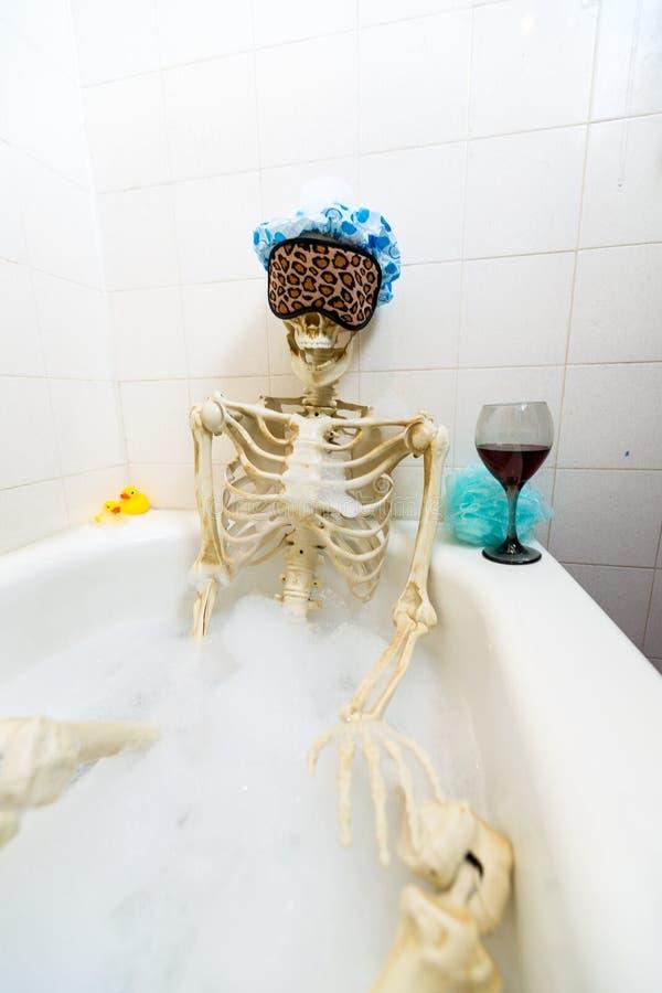 Squelette osseux prenant un bain moussant dans un baquet sale blanc cassé sale images stock
