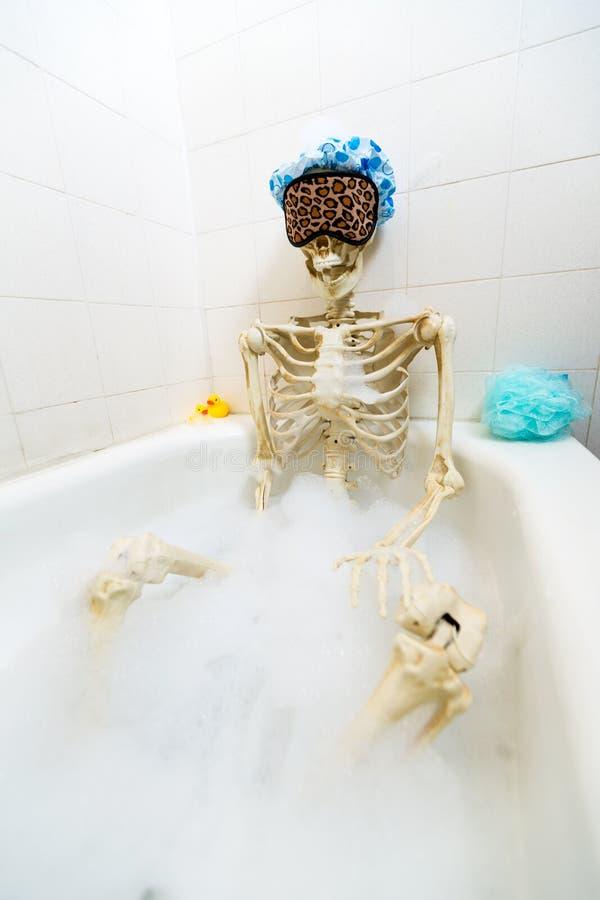 Squelette osseux prenant un bain moussant dans un baquet sale blanc cassé sale image libre de droits