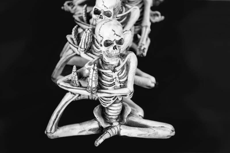 Squelettes dans une rangée faisant le yoga avec un pied sous leurs bras photos libres de droits