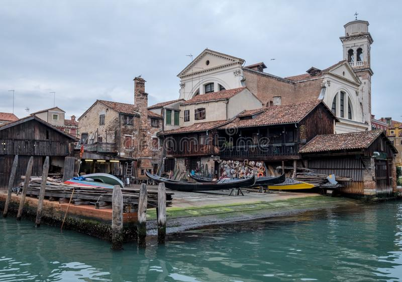 Squero di San Trovaso in Venice Italy. Historic gondola boatyard in Venice. Venice Italy. Squero di San Trovaso with the Church of San Trovaso in the background royalty free stock photo