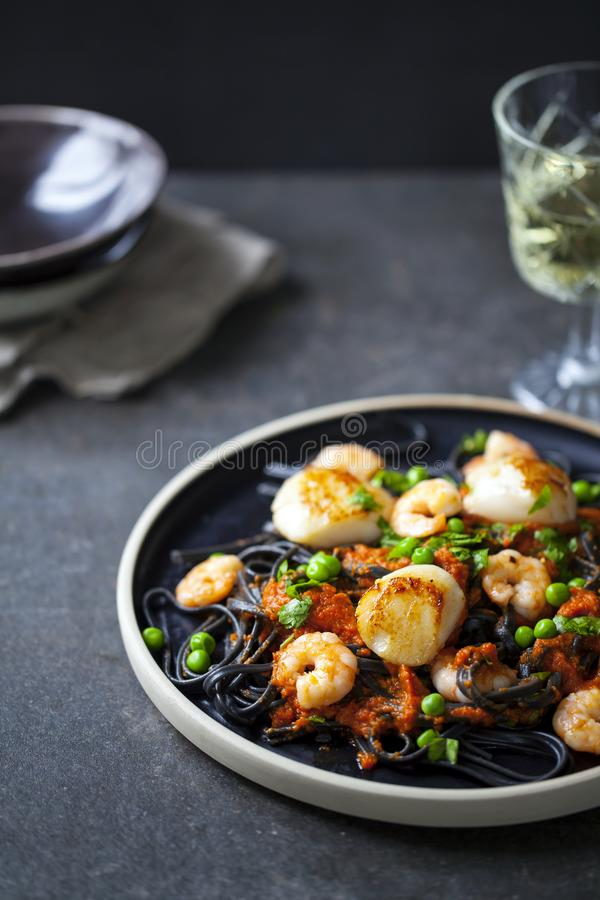 Squid ink pasta with prawns and scallops stock images