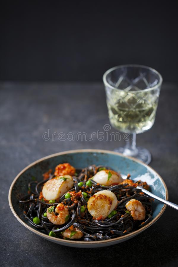 Squid ink pasta with prawns and scallops stock photography