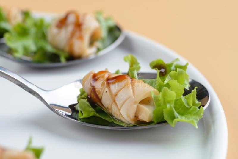 Squid snack on spoon stock photos