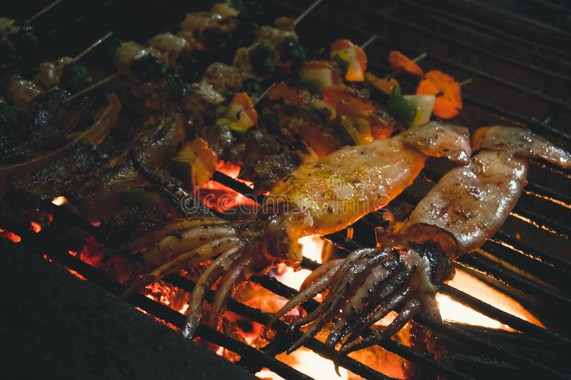 Squids, vegetables, mushrooms, frog, cooked on an open fire in the street. street Vietnamese food stock photo