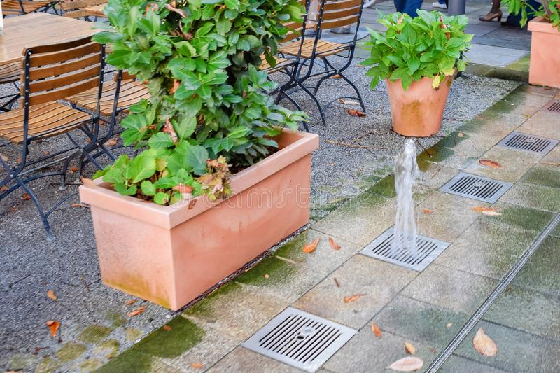 Squirting fountain from lattice in floor near pot with green leaves in cafe in Salzburg Austria. Squirting fountain from lattice in floor near pot with green royalty free stock image
