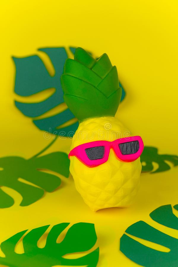 Pineapple in sunglasses on yellow background among paper cut tropical leaves. Squishy toy pineapple in sunglasses on yellow background among paper cut tropical royalty free stock images