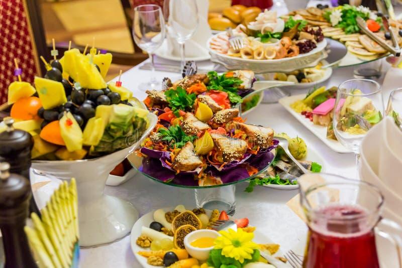 Squisitezze, spuntini e frutta sulla tavola festiva nel ristorante celebrazione approvvigionamento Tabella di banchetto fotografia stock libera da diritti
