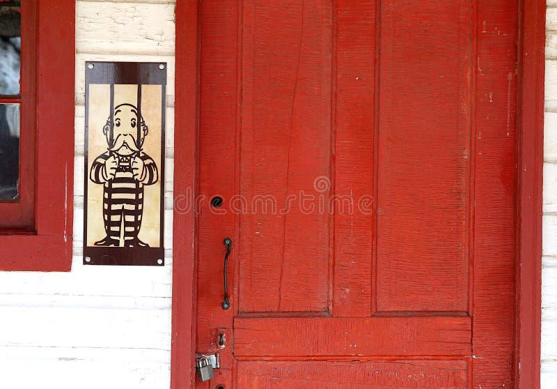 Sr. Homem do monopólio mostrado vestindo um uniforme da cadeia por uma porta vermelha fechado foto de stock royalty free