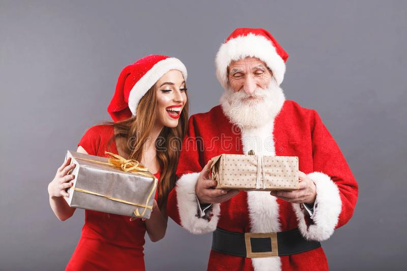 sra. Claus Looking At The Box Santa Is Holding imagens de stock