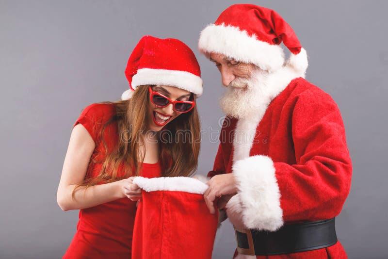 sra. Claus Standing Searching Some Presents em Santa Claus Bag fotografia de stock