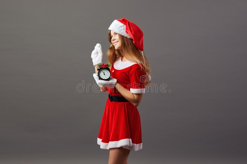Sra. de encantamento Santa Claus vestiu-se na veste vermelha, o chapéu de Santa e as luvas brancas estão guardando um pulso de di fotos de stock royalty free