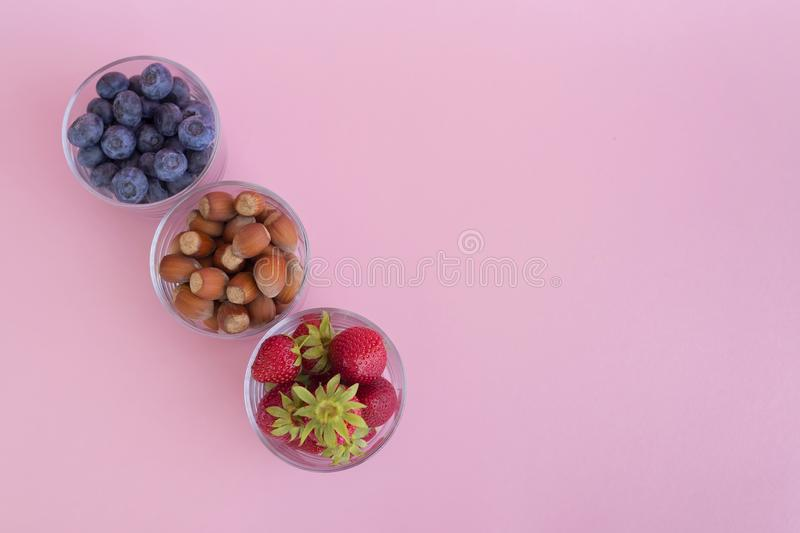 Srawberry, blueberry and hazelnuts in glass cups on pink background. Top view stock photo