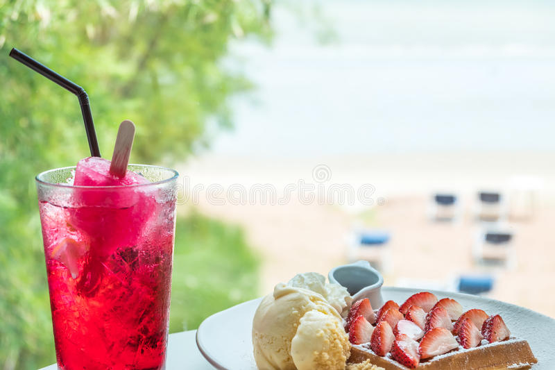 Srawberry waffle with vanilla ice cream and red drink stock images