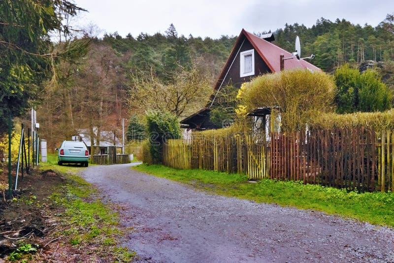 Srbska Kamenice, repubblica Ceca - 8 aprile 2017: copra il cottage dietro un recinto di legno lungo il percorso della ghiaia che  fotografie stock
