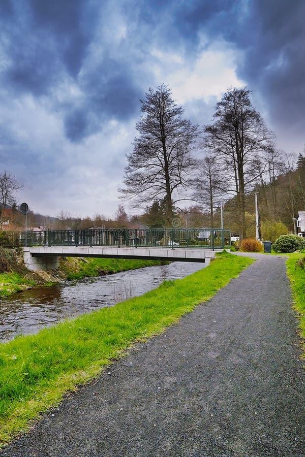 Srbska Kamenice, Tjeckien - April 08, 2017: grusbana som leder till den lilla bron över liten vik Kamenice i naturreserven Arba royaltyfri bild
