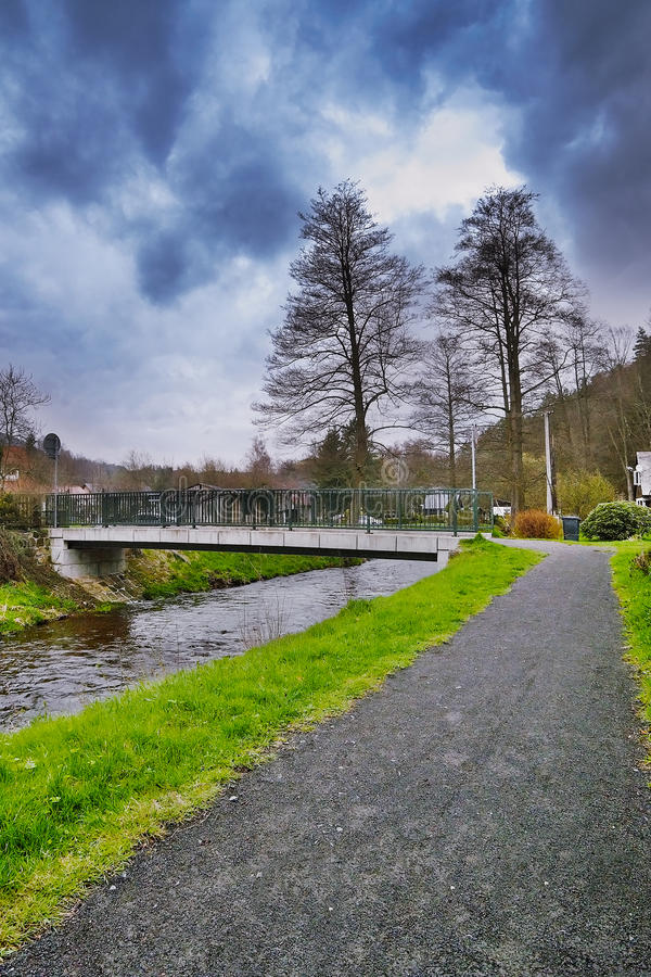Srbska Kamenice, Tsjechische republiek - 08 April, 2017: grintweg die tot kleine brug over kreek Kamenice in natuurreservaat Arba royalty-vrije stock afbeelding