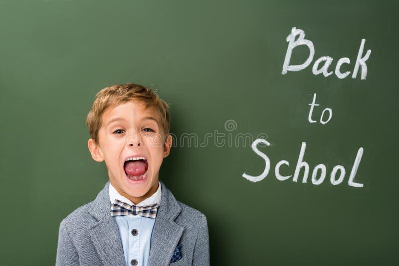 Sreaming-Schüler nahe bei Tafel lizenzfreie stockbilder
